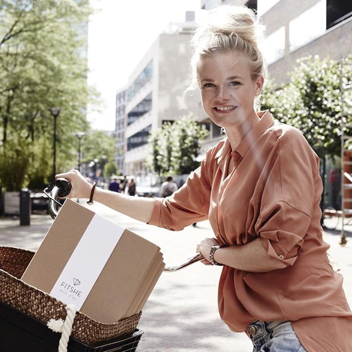 Vrouw op de fiets met vier FITSHE pakketten in het mandje van haar fiets