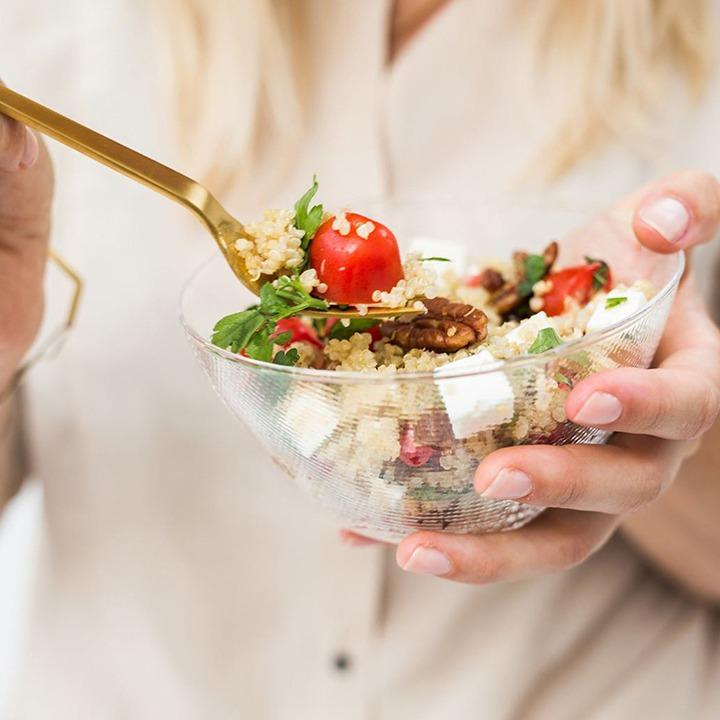 Closeup van een bak met een quinoa salade vastgehouden door een vrouw