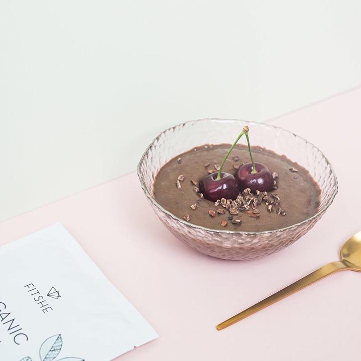 FITSHE zakje met chocoladesmaak eiwitpoeder naast een kom met een maaltijd