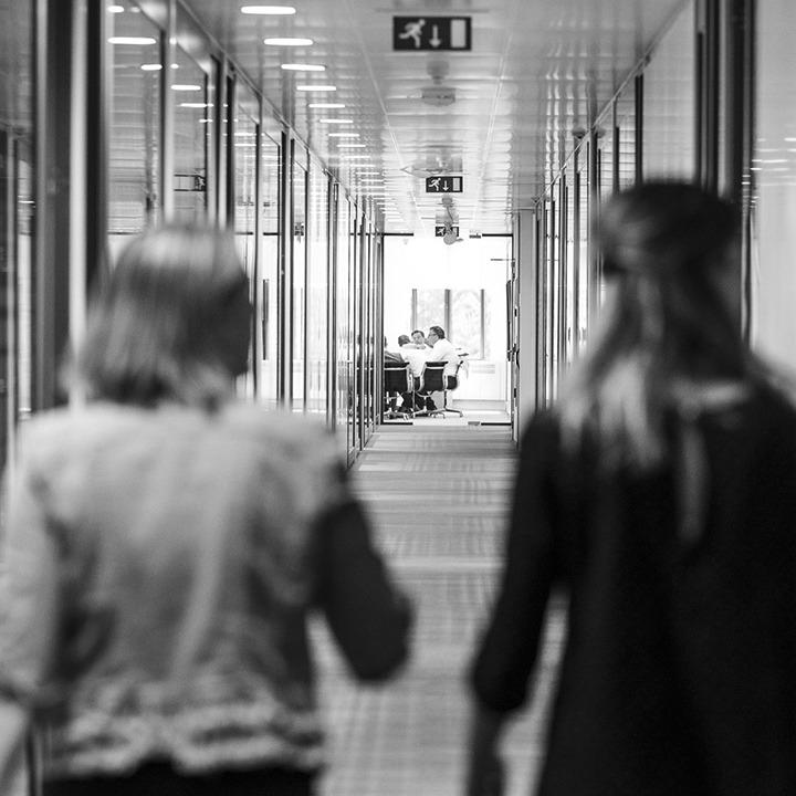 Zwart wit afbeelding van twee HVK Stevens medewerkers die door de gang lopen