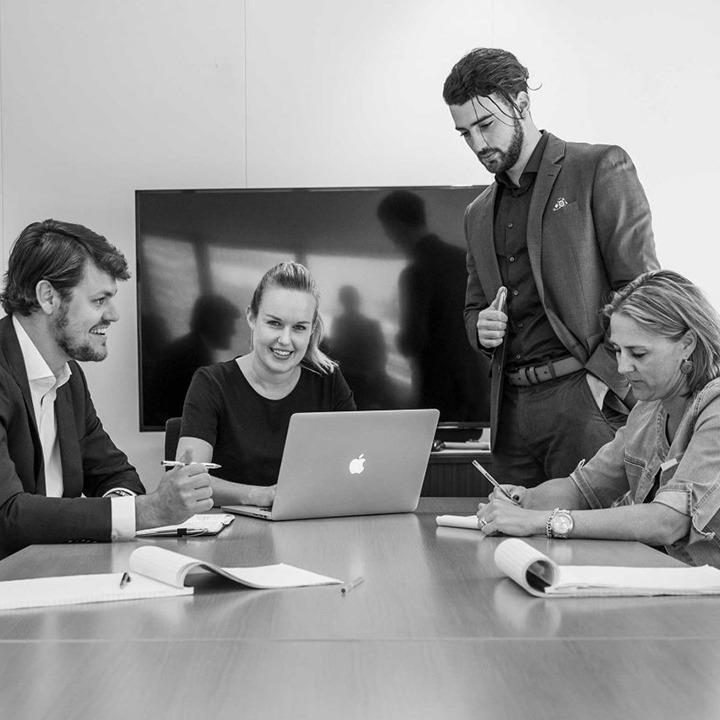 Zwart wit afbeelding van vier HVK Stevens medewerkers tijdens een overleg