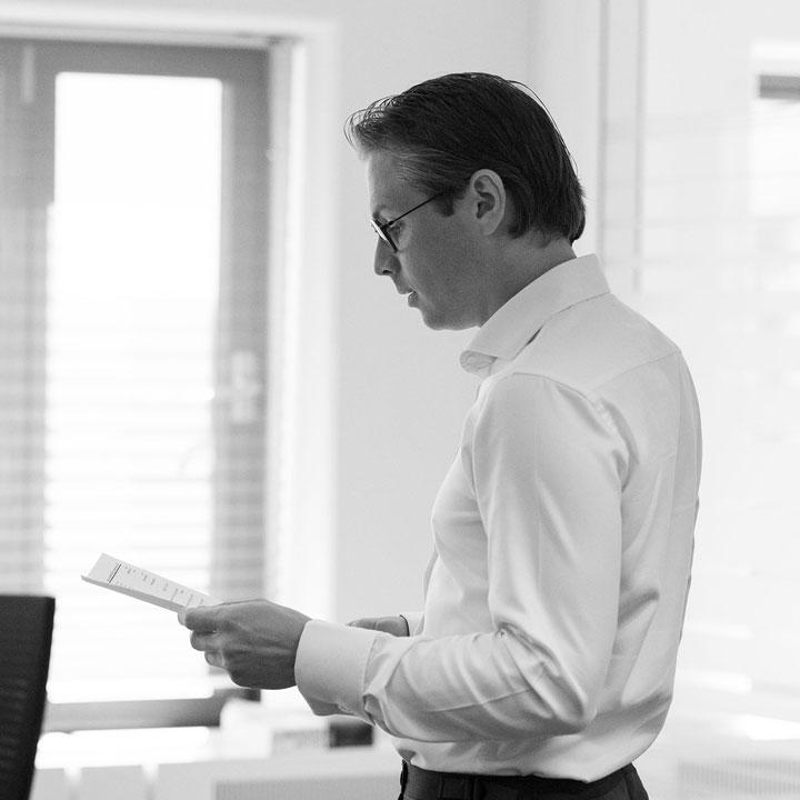 Zwart wit afbeelding van een HVK Stevens medewerker met een papier in zijn hand