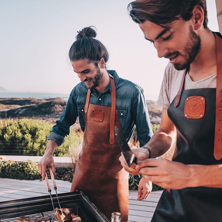 Twee mannen naast een barbecue in een WITLOFT schort