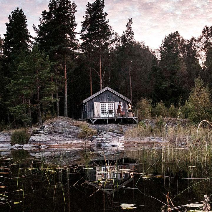 Sfeerafbeelding van een boshut in Zweden met de bewoner op de veranda in WITLOFT schort