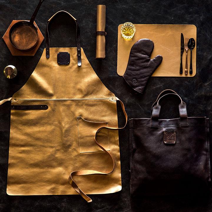 WITLOFT leren goudkleurig schort naast een ovenwant, placemat en shopper