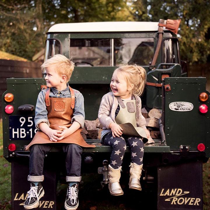 Twee kinderen in WITLOFT schort zittend in de laadbak van een pickup auto