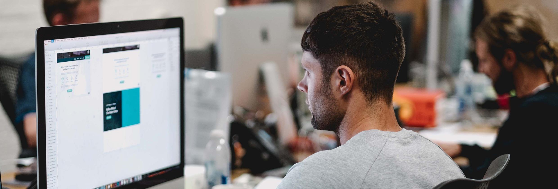 Grafisch ontwerper bezig met ontwerpen op zijn iMac