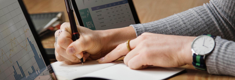 Marketeer die bezig is om website statistieken te noteren op papier